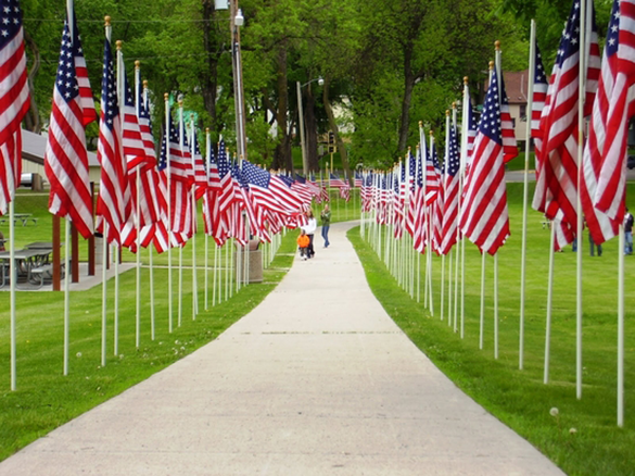 Picture of sidewalk flanked on two sides by US flags