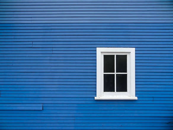 A single white-paned window on a blue wall of a house