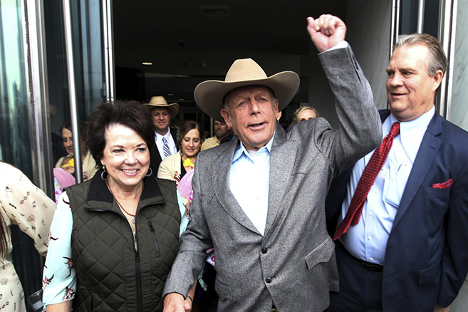 Picture of Cliven Bundy exiting the federal courthouse, with a fist raised in the air triumphantly