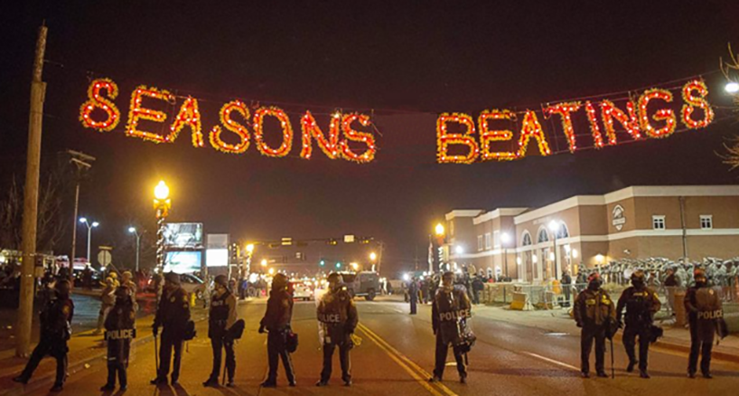 "Picture of police in riot gear standing under lights that read ""Seasons Beatings"""