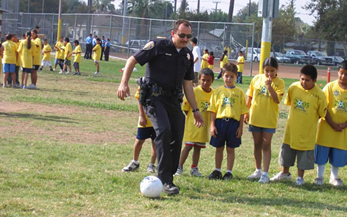 Picture of police officer kicking a soccer ball with local children