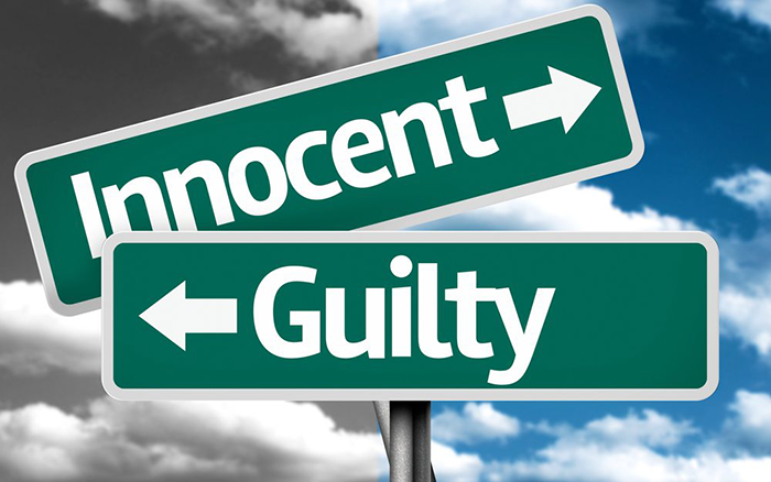 "Picture of 2 street signs, one says ""Innocent"" and the other says ""Guilty"""