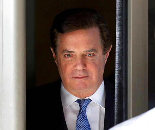 Picture of Paul Manafort standing in a doorway, wearing a white shirt, blue tie, and black suit jacket