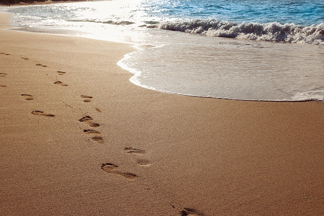 Picture of footprints in the sand by the ocean