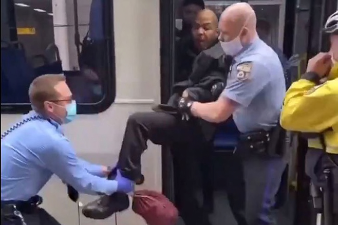 A still image from a video of a SEPTA passenger being ripped off the bus by several police officers